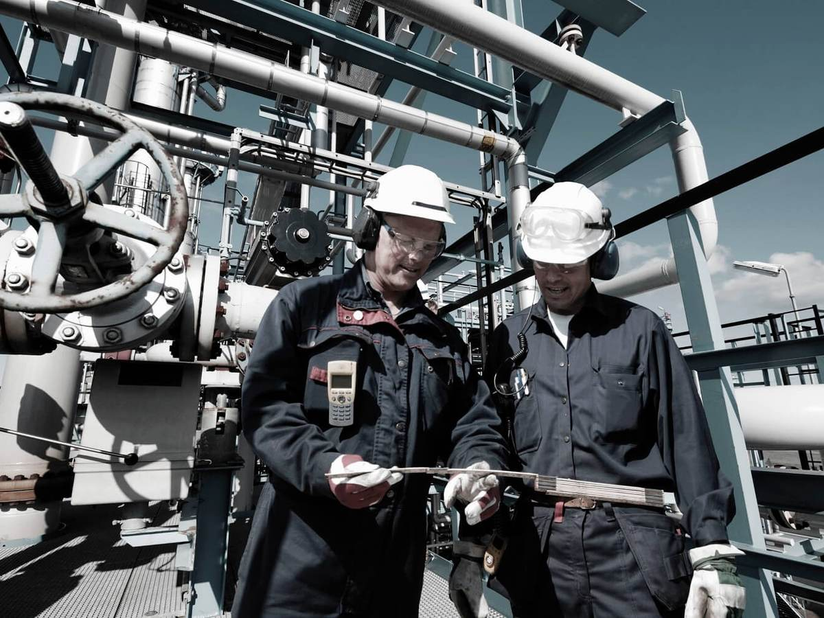 Oil and gas workers confer inside large refinery industry