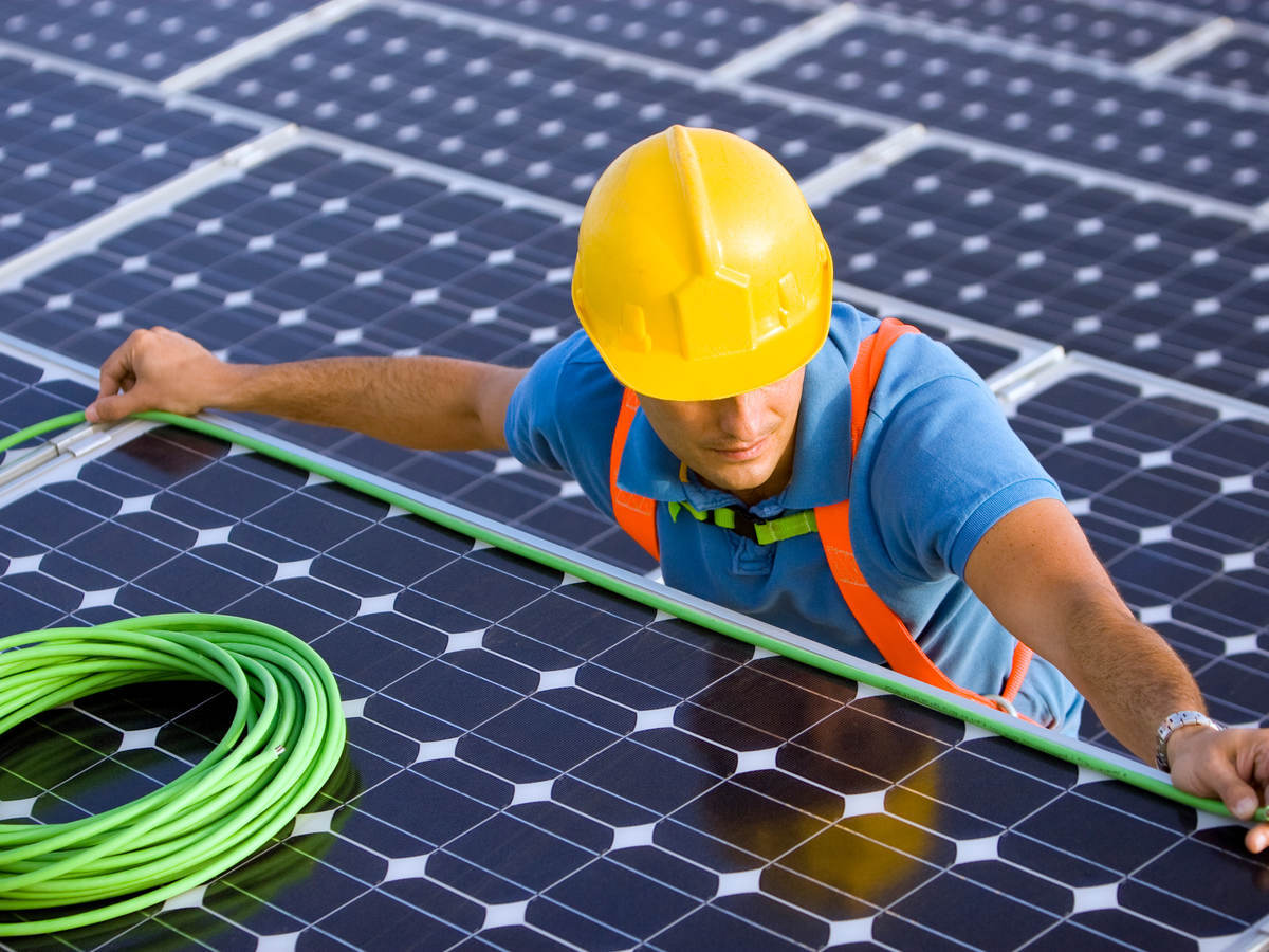 man in hard hat doing wiring on a solar energy panel for wire and cable testing and certification