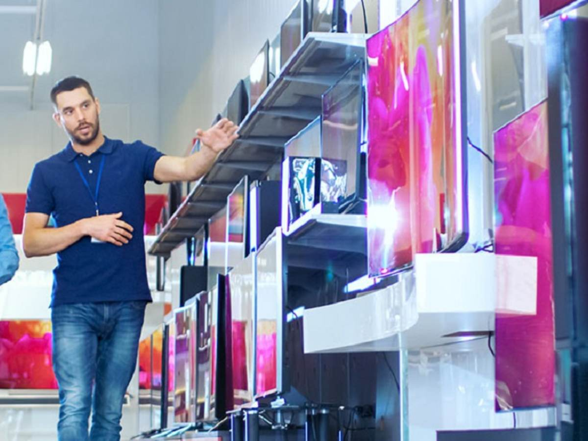Sales person standing next to consumer electronics display in retail store