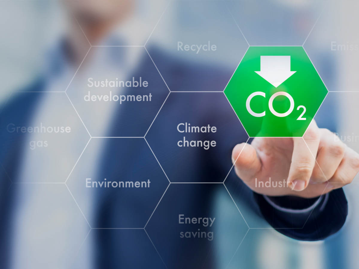Man in suit jacket touching a CO2 icon with his fingertip to indicate embodied carbon.