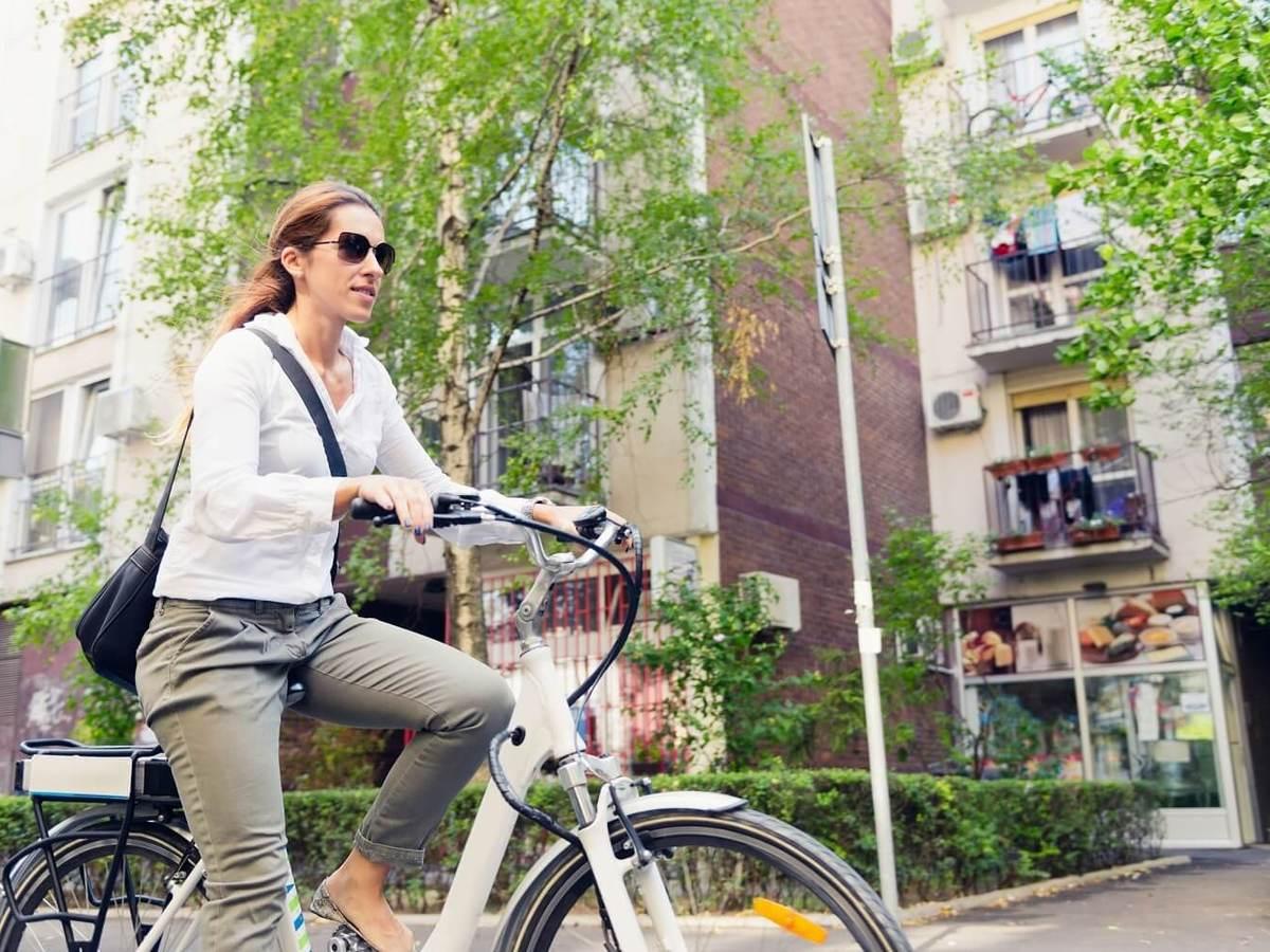 E-bike commuter, riding through a city block