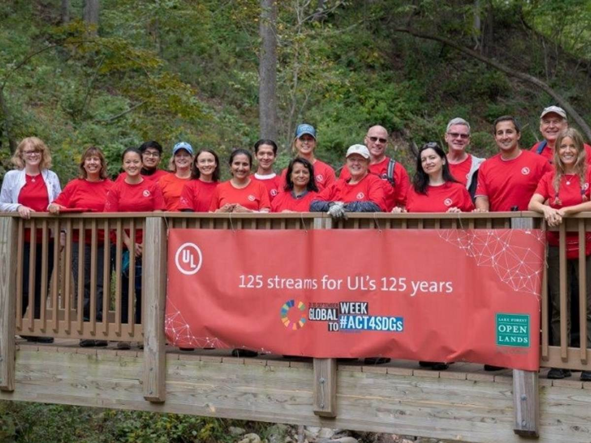 UL employees proudly pose on a wooden bridge on which has been hung a banner announcing 125 streams for 125 years.