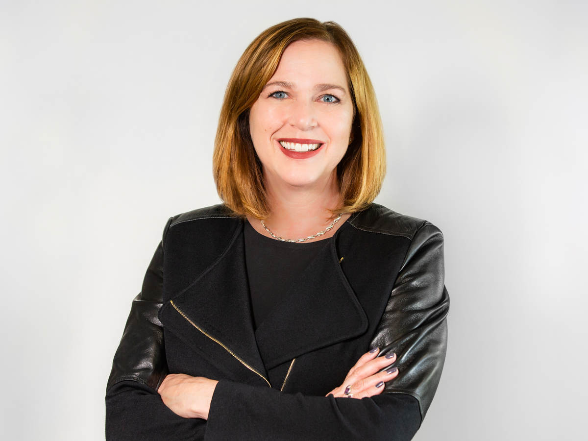 Jen Scanlon, CEO of UL, poses in front of a grey background wearing a black jacket and black dress