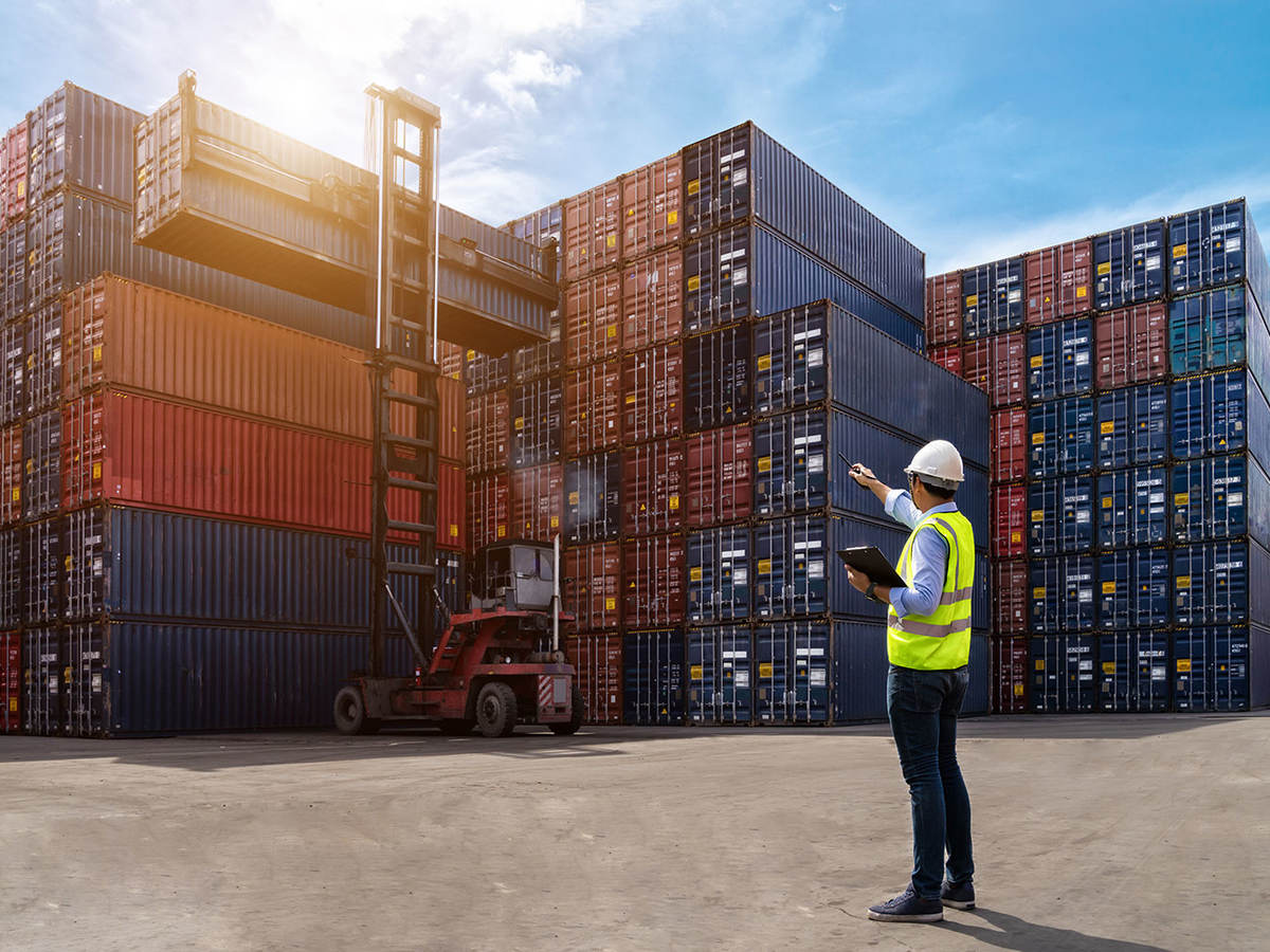 Image of a man in reflective vest directing placement of shipping containers in a shipyard.