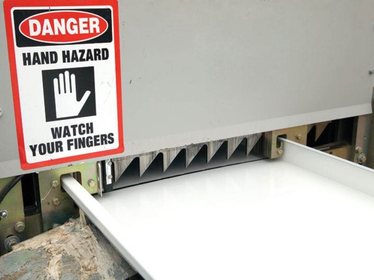 An industrial machine with a watch for fingers hazard sign warning facility workers.