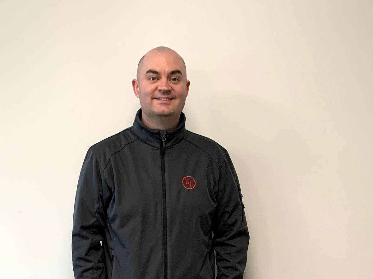 Seán Flannagan poses for EWeek picture. He's wearing a dark grey jacket with the red UL logo on its left pocket.