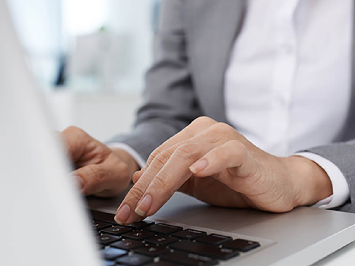 Photo of a woman typing on a laptop