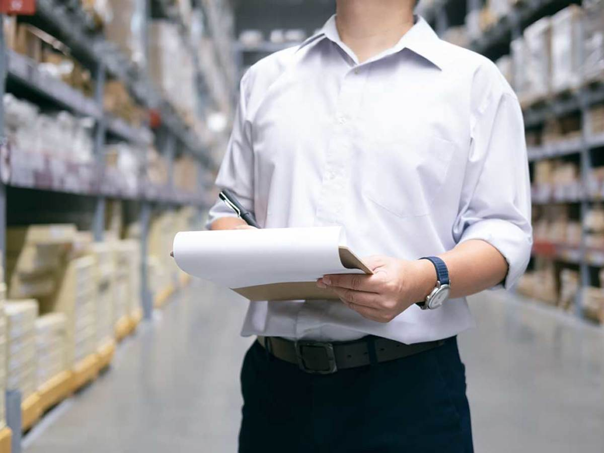 Man checking items on a clipboard in a warehouse