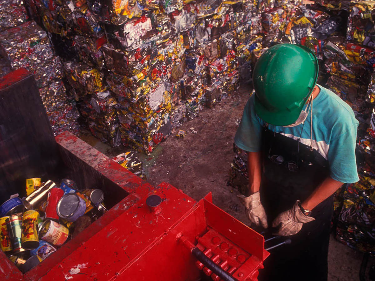 Man working trash compactor in landfill