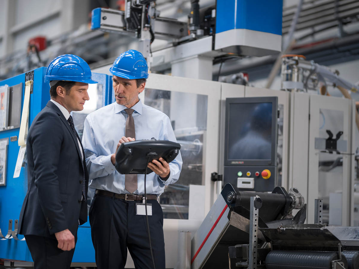 Businessmen with a digital tablet talking in a factory