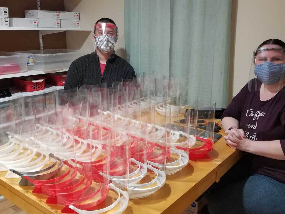 Ed and Brandi Miller sit on either side of a table filled with red and white face shields