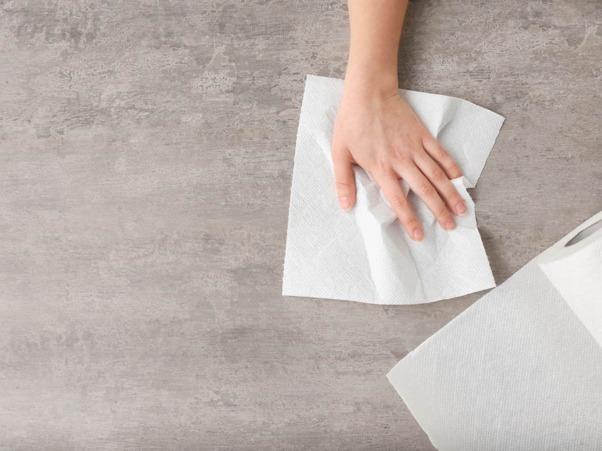 Woman wipes counter with a white paper towel.