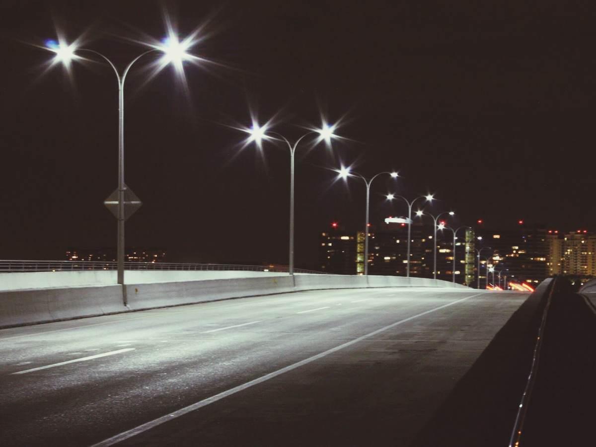 Streetlights at night on quiet road.