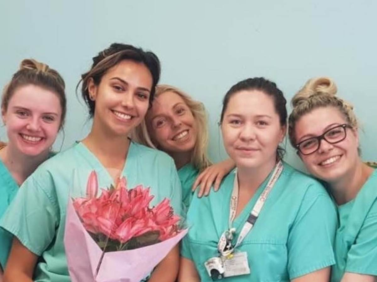 Five nurses wearing green scrubs, one who is holding a bouquet of flowers, pose for a picture.