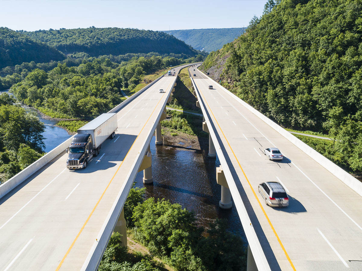 Aerial view of two separate highway bridges with cars and trucks traveling in both directions
