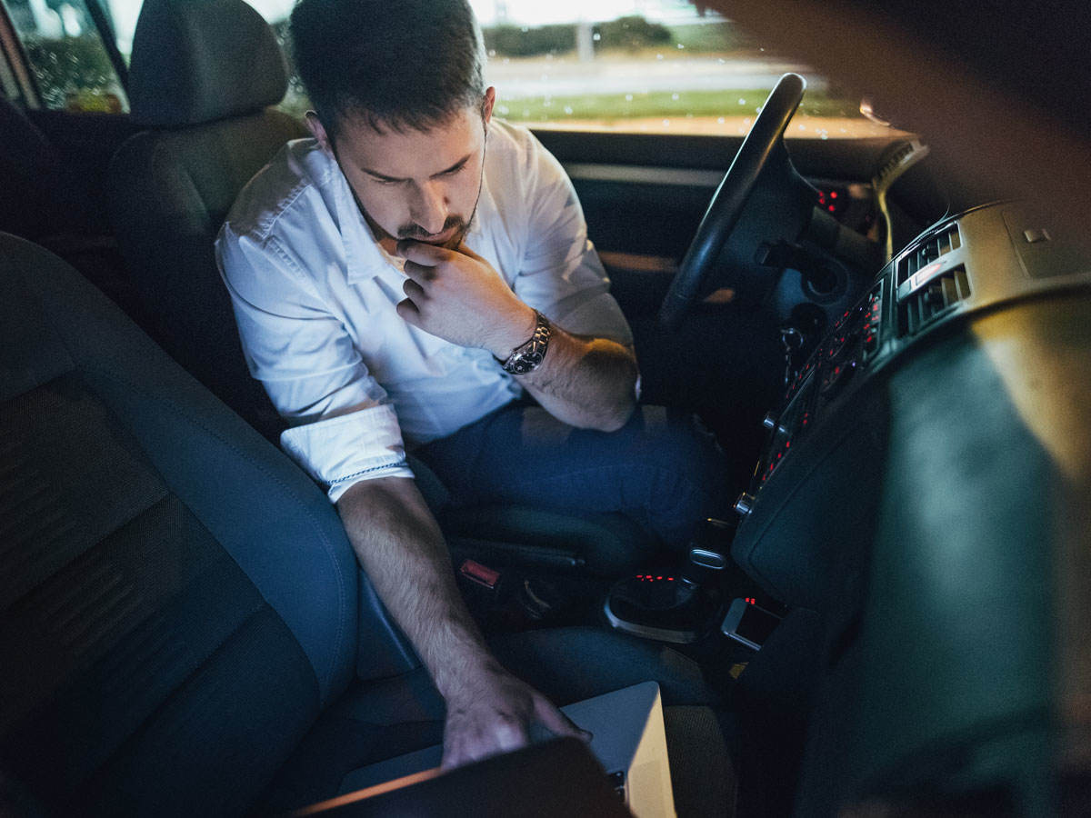 Man in parked car looking at a laptop in the passenger seat
