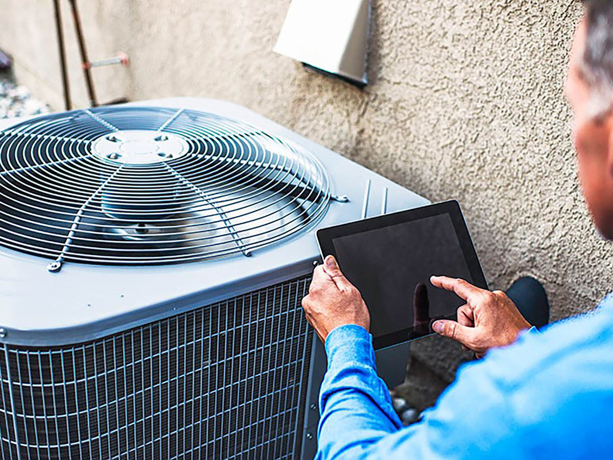Maintenance engineer using a digital tablet to inspect air conditioning unit