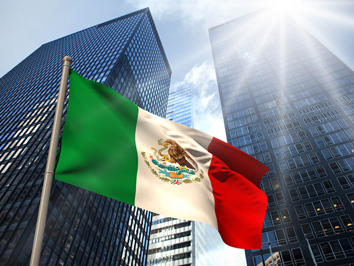 Mexico flag in front of tall sky scrapers