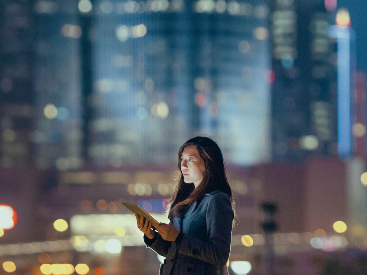 Woman outside on rooftop alone with cityscape in the background.