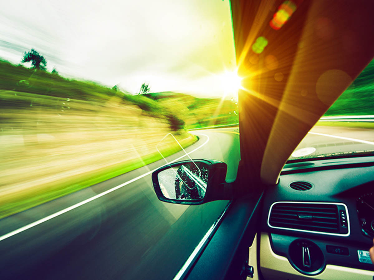 View out of a car on a road with sunlight by left side of the windshield