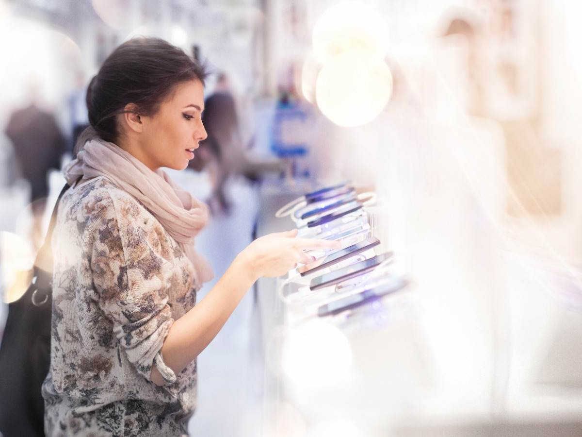 Consumer looking at several mobile devices in retail setting