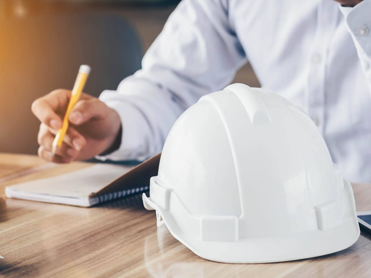 Photo of a person making notes, hard hat in foreground