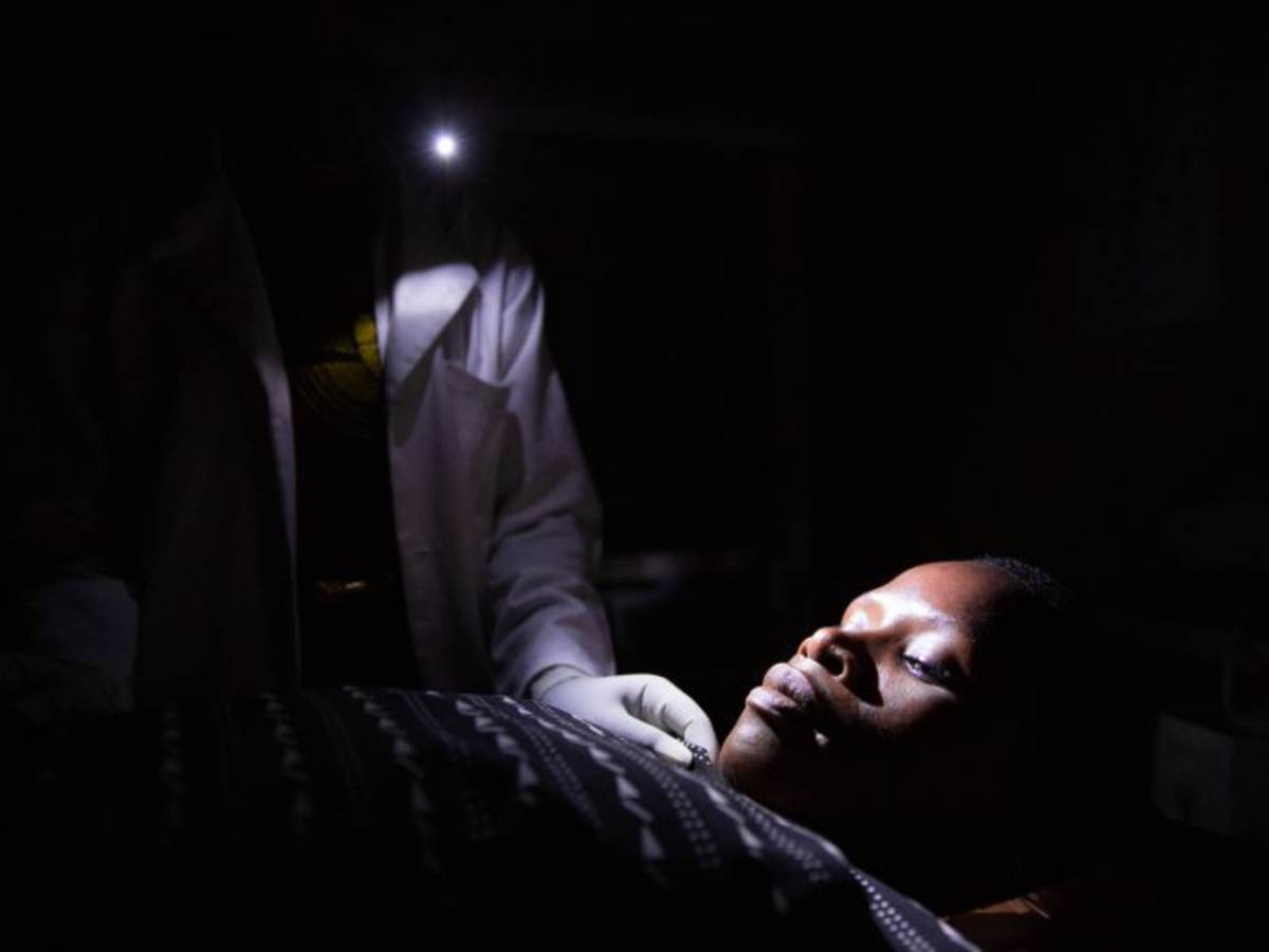 Tanzania midwife at night holding cellphone light over female patient