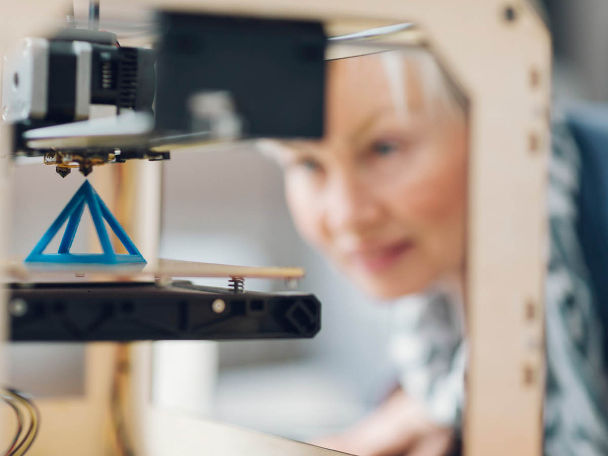 Photo of a woman working by a 3D printer