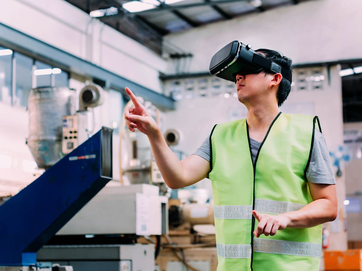 Manufacturing engineer wearing VR goggle headset in virtual reality simulation