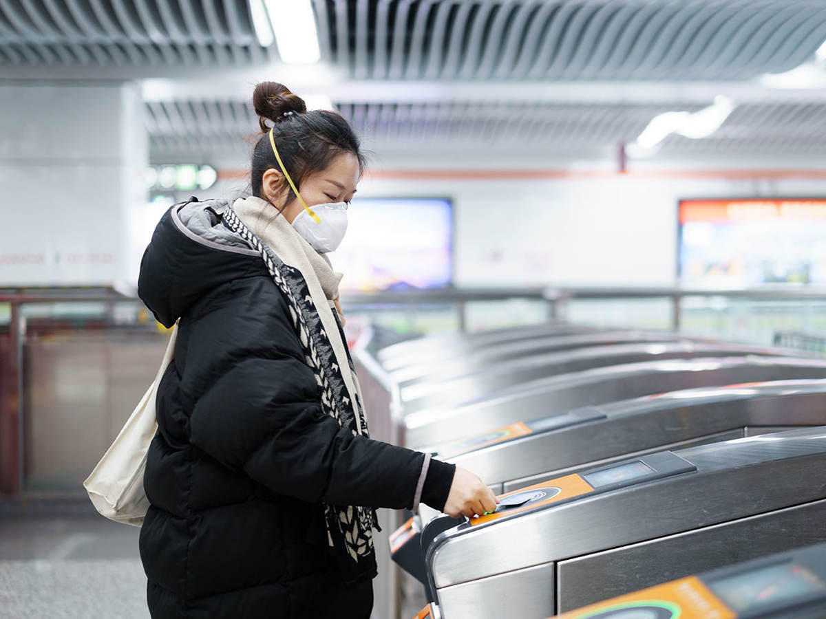 Woman wearing a mask paying to use the subway