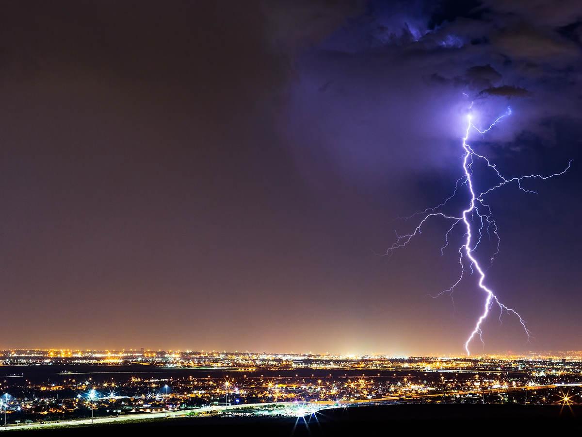 lightning striking cityscape at night