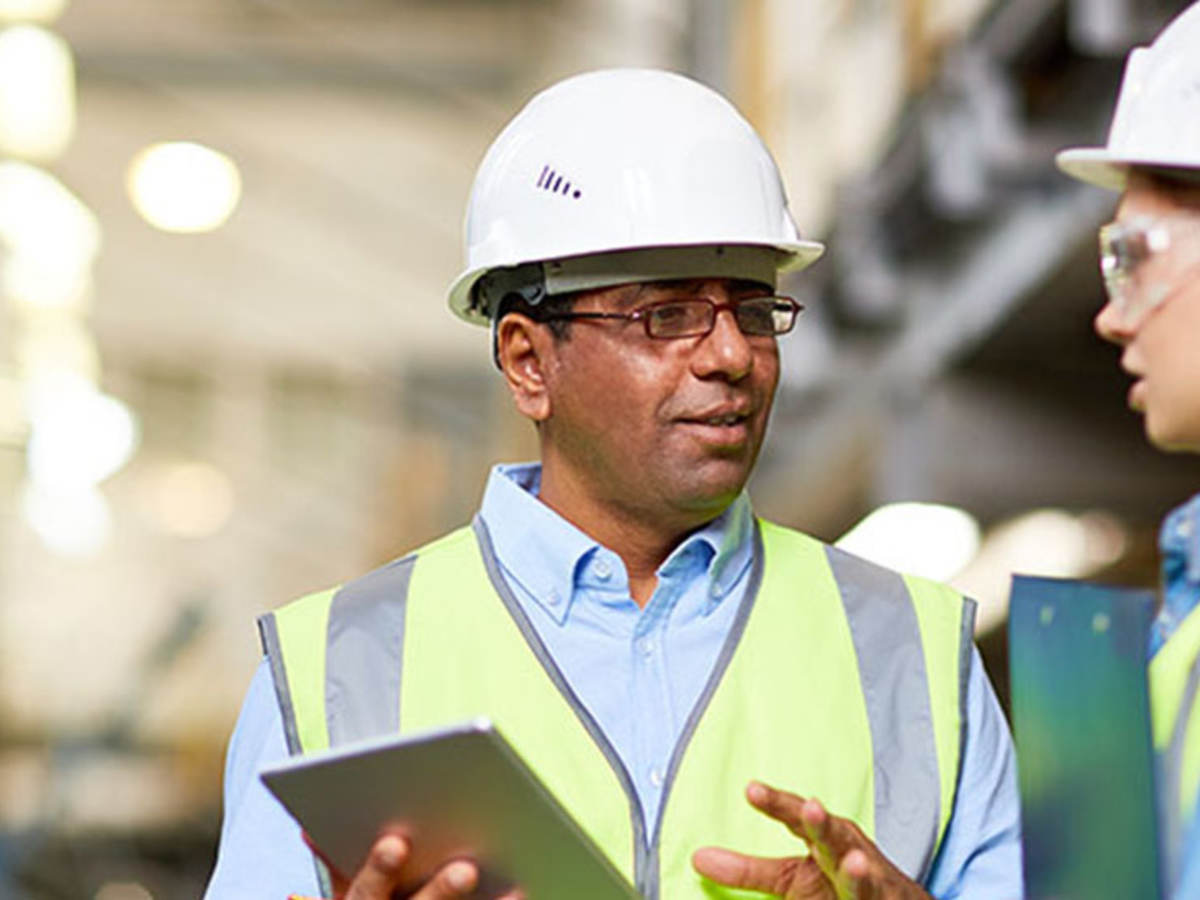 workers talking in warehouse while holding tablet