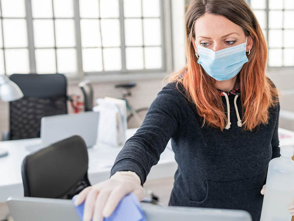 Photo of a woman cleaning a monitor
