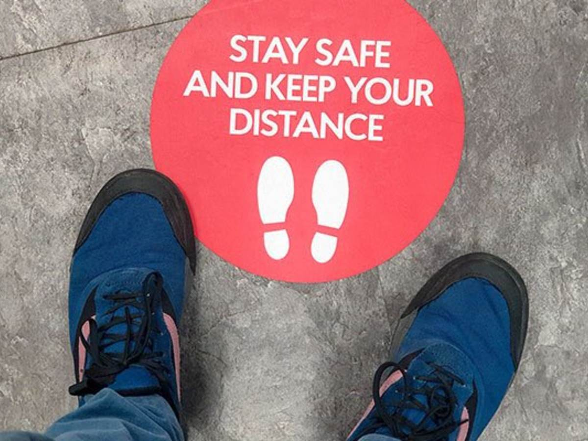 Two feet stand in front of a floor graphic that says stay safe and keep your distance