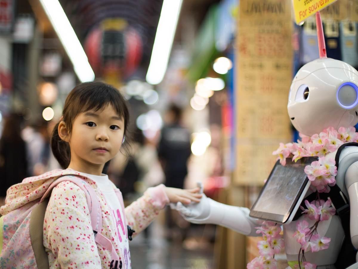 Asian girl touching robot's hand