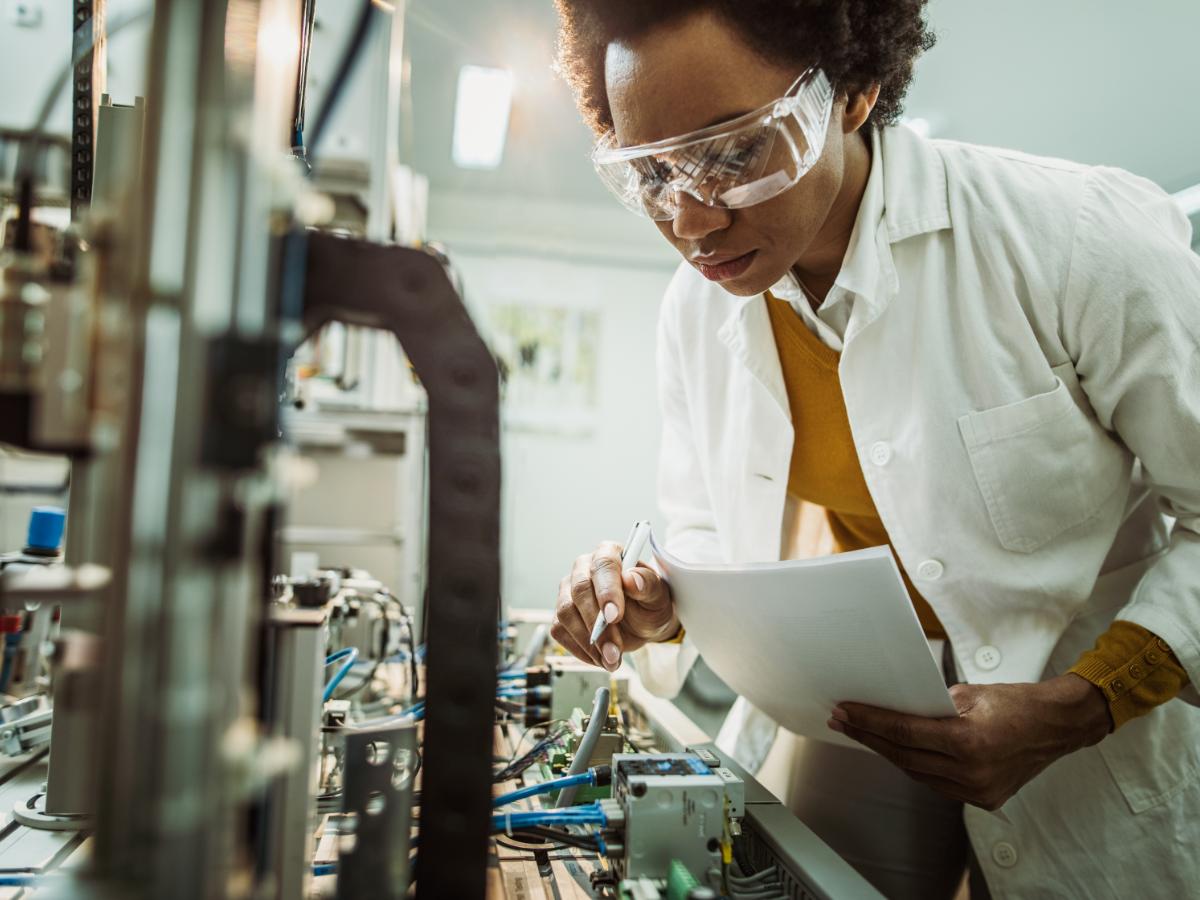 Female engineer working on industrial machine in laboratory