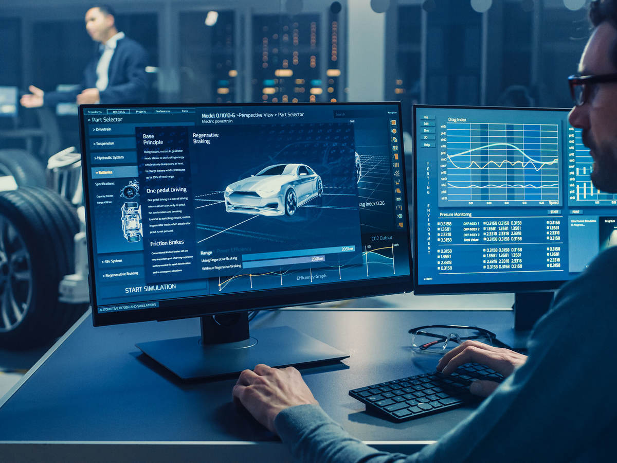 Automotive engineer looking at a computer displaying a 3D electric car chassis prototype with wheels.