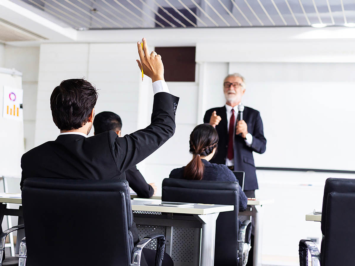 Business man raising hand in a classroom setting