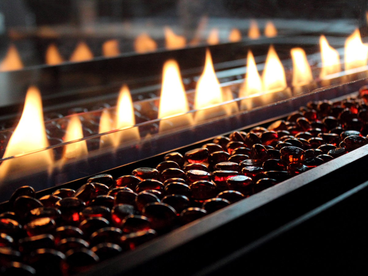 A row of flames burn within a gas fireplace