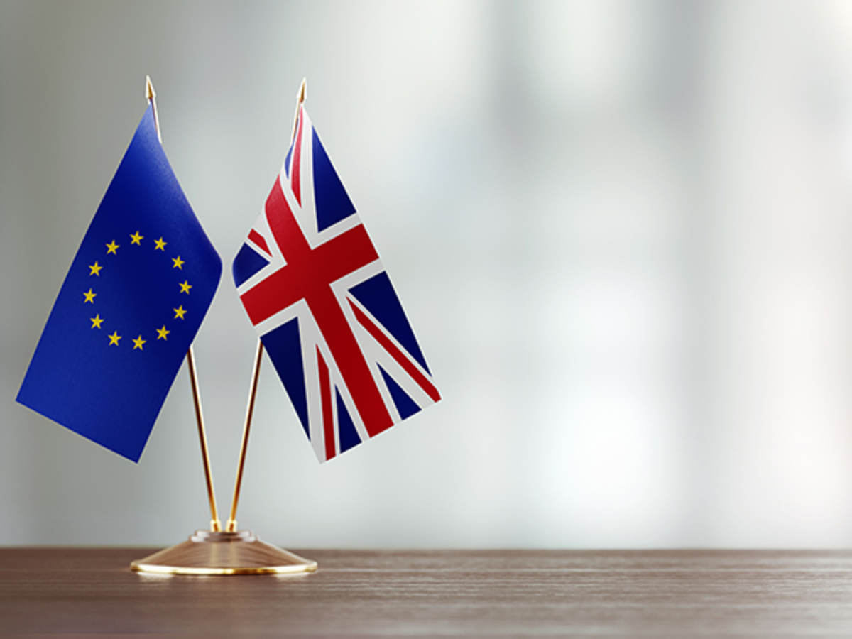 European union and British flag pair on a desk over defocused background