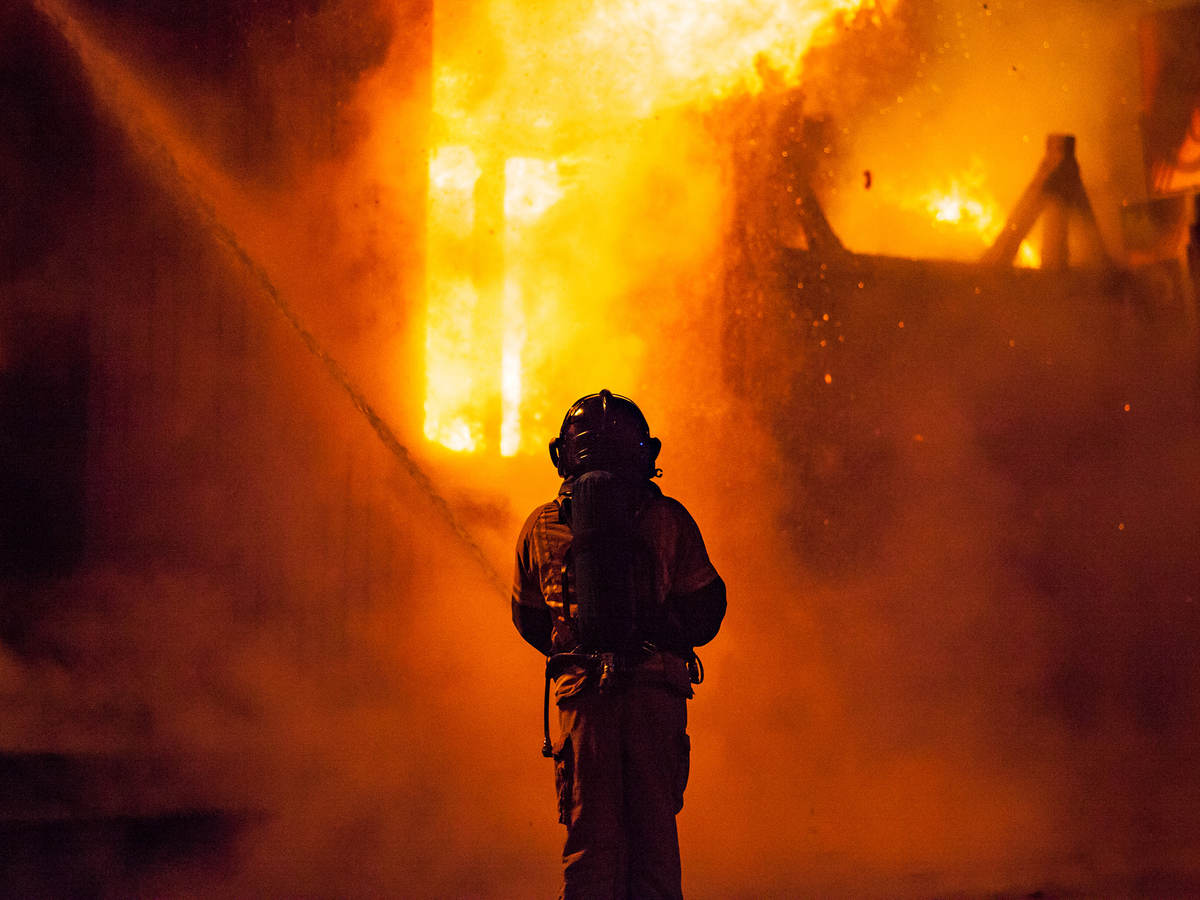 A firefighter sprays water on the outside of a burning building
