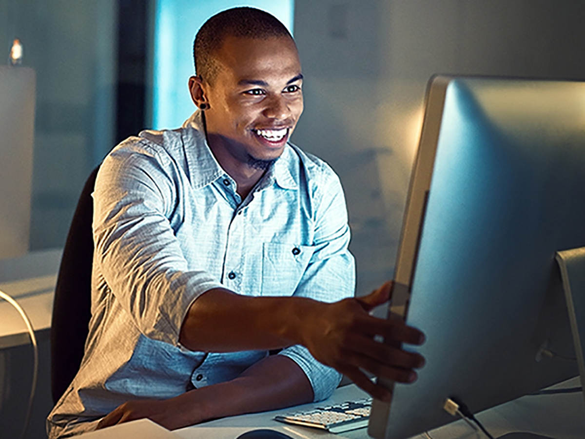 Smiling man sitting at a desk in front of a computer monitor