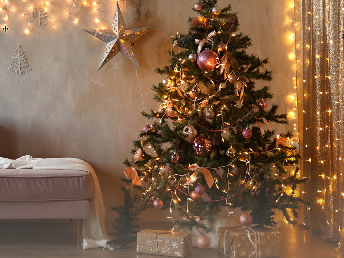 A living room with pre-lit Christmas tree and other lit decorations
