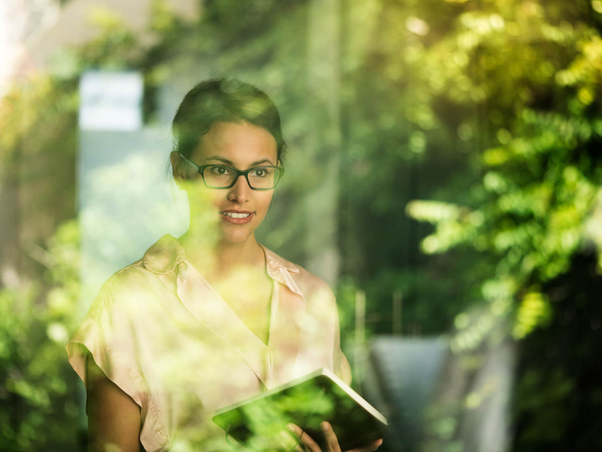 A woman stands at a window with reflected greenery.