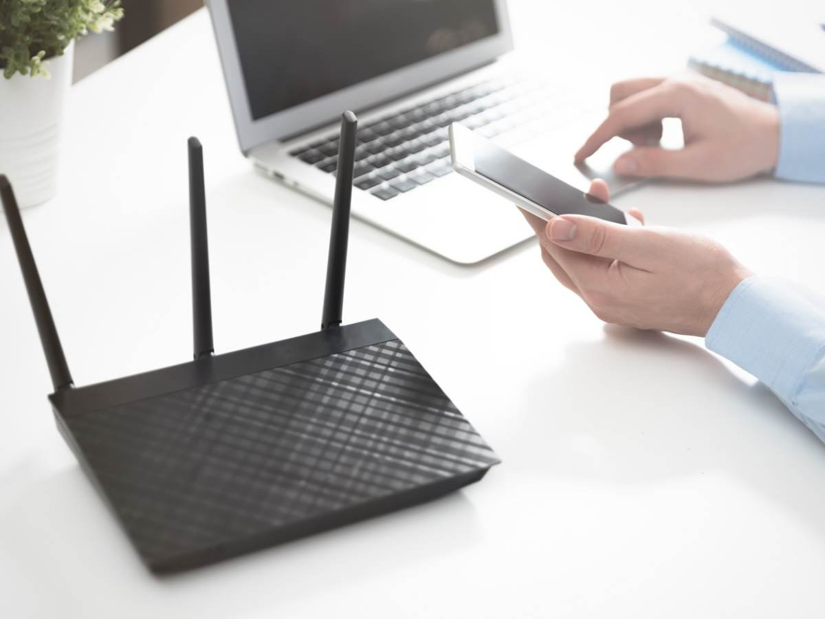 Wireless router positioned next to a laptop and mobile phone on a white table.