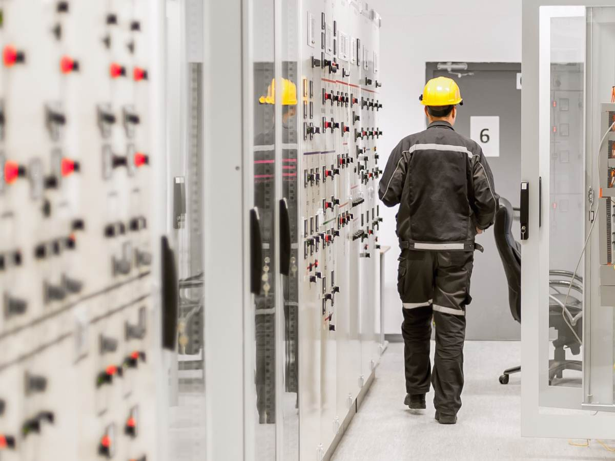 Engineer using protective relay and medium voltage switchgear in a bay control unit.