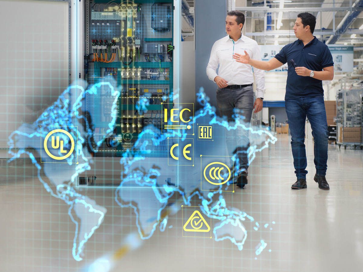 Two men walking down factory floor with a control panel to their right. An overlay of a world map with various safety marks.
