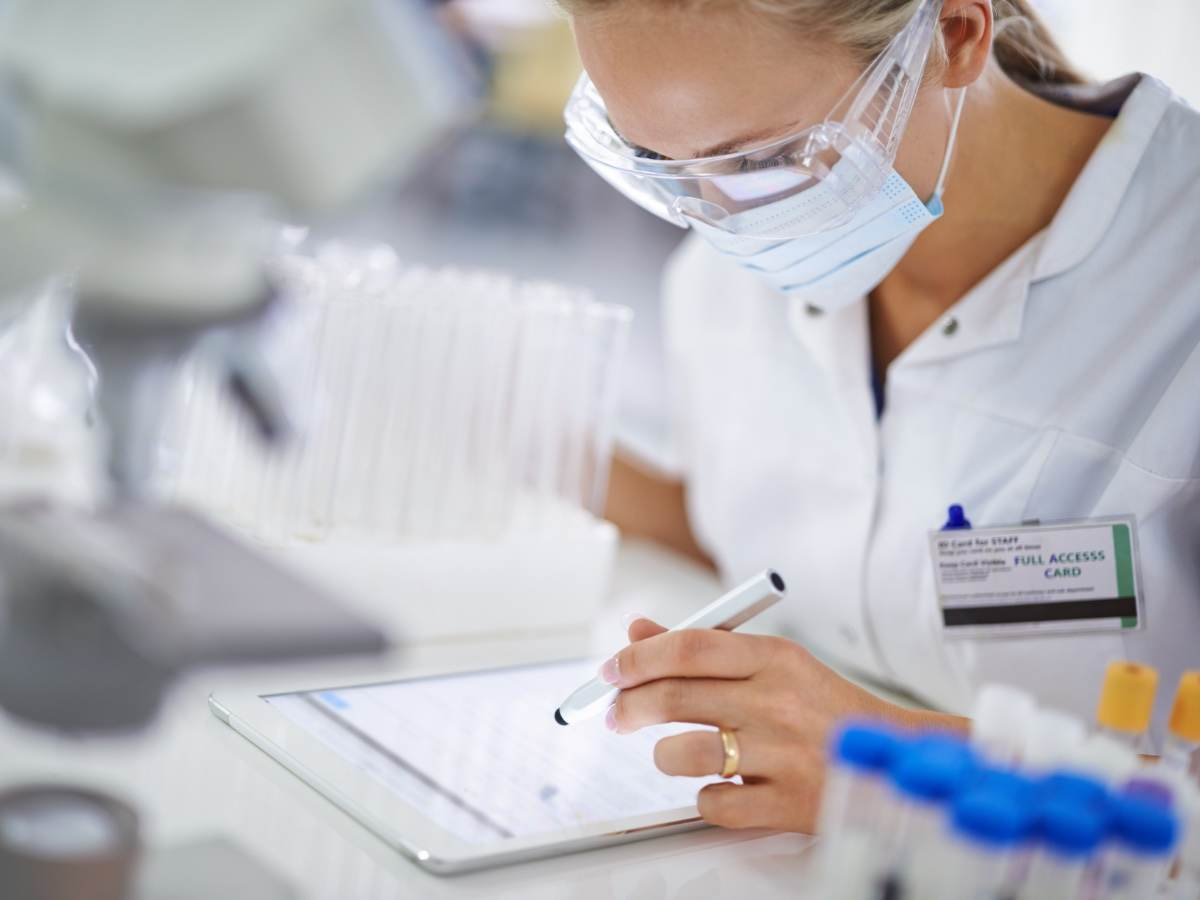Female medical professional wearing protective eyewear and facemask making notes on electronic device
