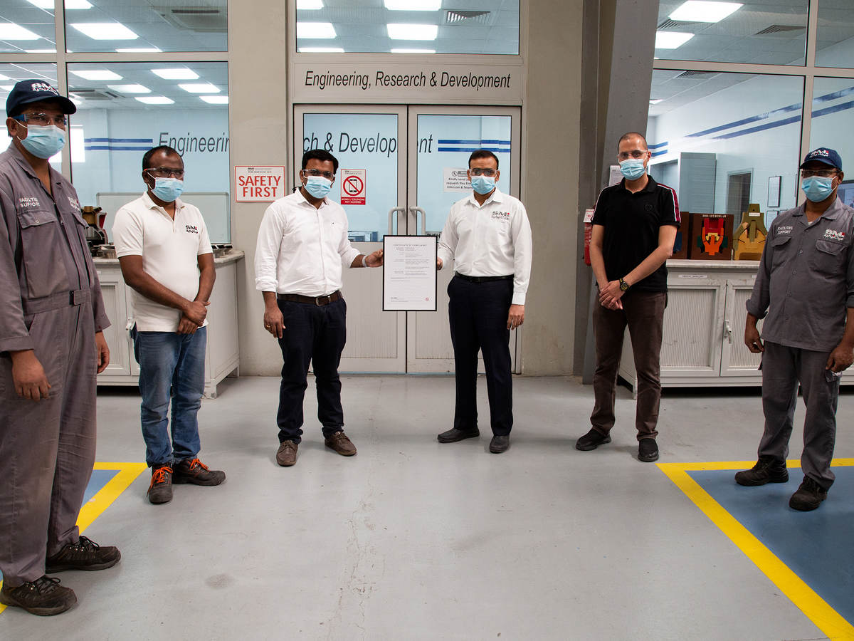 Saudi Mechanical Industries manufacturing facility in Saudi Arabia staff holding certificate