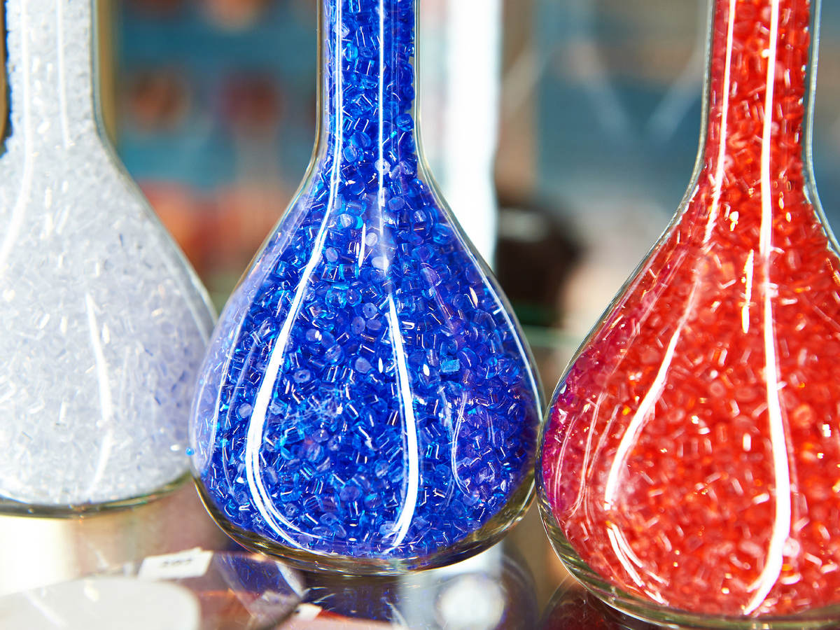 Colorful plastic granular polymer in glass flasks